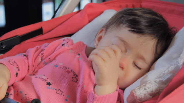 cu baby girl (6-11 months) sleeping in stroller, sucking her thumb and then taking her thumb out of her mouth / miami, florida, usa - 6 11 months stock videos & royalty-free footage
