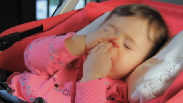cu baby girl (6-11 months) sleeping in stroller, sucking her thumb / miami, florida, usa - 6 11 monate stock-videos und b-roll-filmmaterial