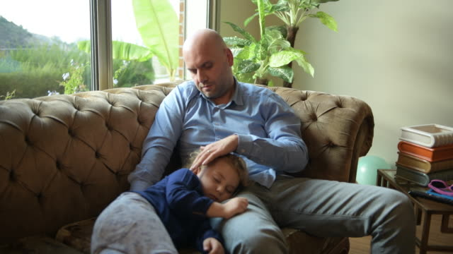 baby girl sleeping on her father's lap - single father stock videos & royalty-free footage
