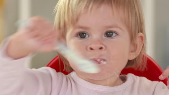 vidéos et rushes de hd: bébé fille souriant et s'amusant tout en mangeant - 18 23 mois