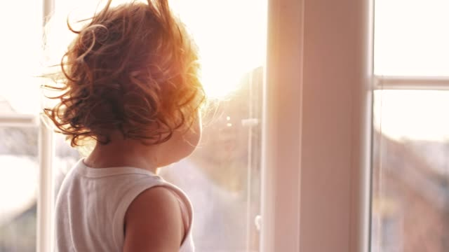 baby girl standing by the window - window stock videos & royalty-free footage