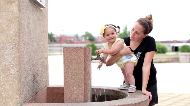 vídeos de stock e filmes b-roll de baby girl (12-18 months) standing on a public water tap, trying to catch water jet and laughing - andar em bico de pés