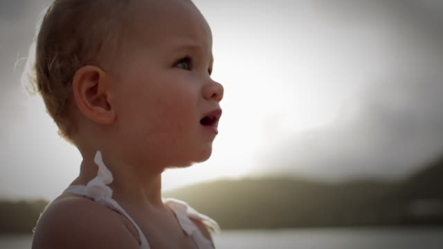 cu td baby girl (18-23 months) standing on pier playing with hands, ocean in background / st marys, antigua, antigua and barbuda - primi passi video stock e b–roll