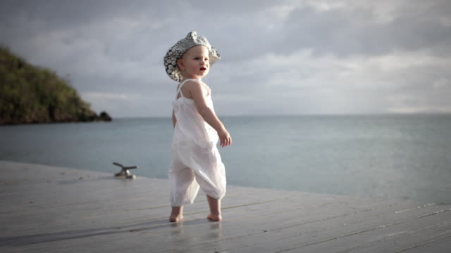 ws baby girl (18-23 months) standing on pier with ocean in background / st marys, antigua, antigua and barbuda - 18 23 months stock videos & royalty-free footage