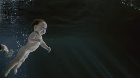 stockvideo's en b-roll-footage met ws slo mo baby girl (18-23 months) swimming underwater / london, united kingdom - babymeisjes