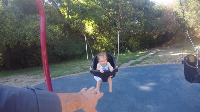 A baby girl swinging outdoors in a park with her father on a sunny day.