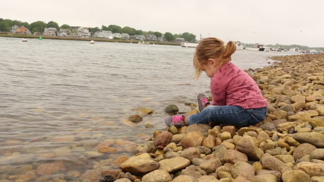 A baby girl throwing small rocks into the water on a cloudy day.