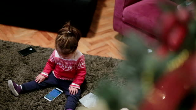 Baby girl under a Christmas tree using the phone