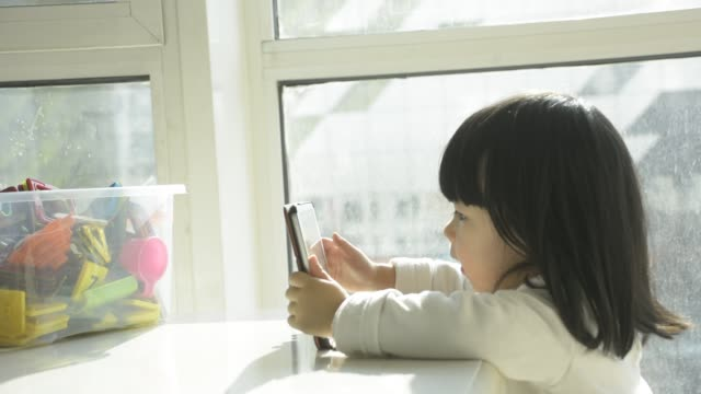 baby girl using digital tablet at home