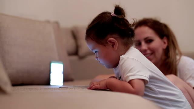 使用してスマート フォン - 触れると画面上を見て女の赤ちゃん - 赤ちゃんの靴点の映像素材/bロール