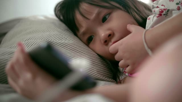 cu : baby girl(4-5 years) using smartphone on bed - 4 5 years stock videos & royalty-free footage
