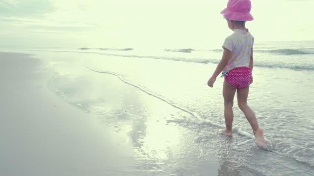 vídeos y material grabado en eventos de stock de niña caminando en la playa - accesorio de cabeza