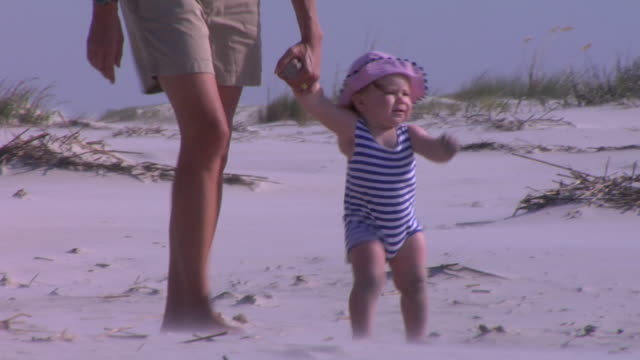 cu, pan, baby girl (12-17 months) walking on beach with mother, st. simons, glynn county, georgia, usa - 12 17 months stock videos & royalty-free footage