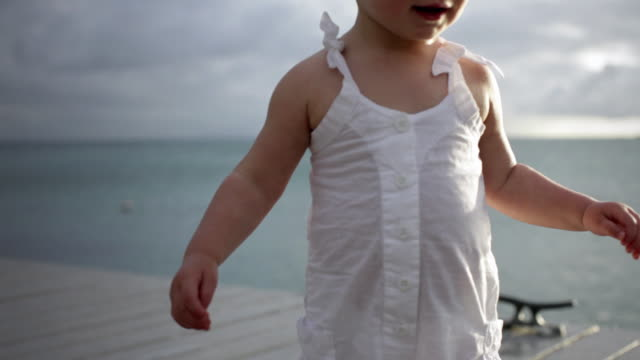 cu td baby girl (18-23 months) walking on pier with the ocean in background / st marys, antigua, antigua and barbuda - 18 23 months stock videos and b-roll footage