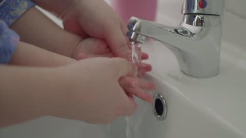 vidéos et rushes de lavage main de bébé fille - laver
