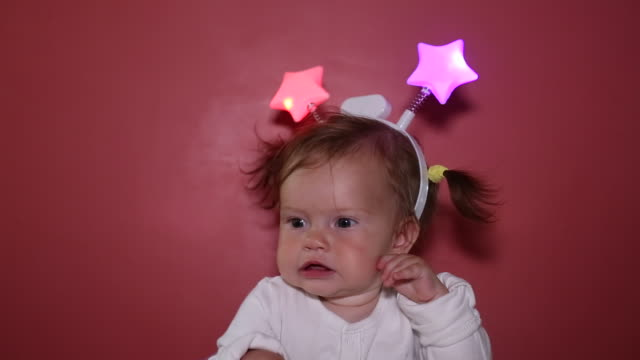 A baby girl wearing a star headband indoors and smiling.