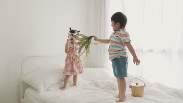 赤ちゃんの女の子の身に着けている牛のマスクを演技と彼女の兄と一緒に牛のような草を食べる - 扮装点の映像素材/bロール