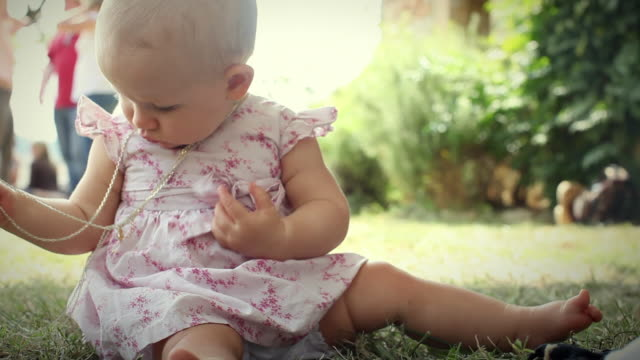 MS Baby girl (6-11 months) wearing dress and necklace sitting on grass / St. Antonin Noble Val, Pyrenees, France