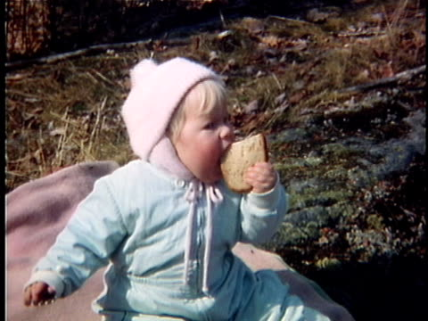 1963 MS Baby girl wearing snowsuit eating sandwich, Middlebury, Vermont, USA