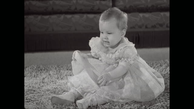 ms baby girl wears dress and sitting on rug, playing with ball / united states - one baby girl only stock videos & royalty-free footage