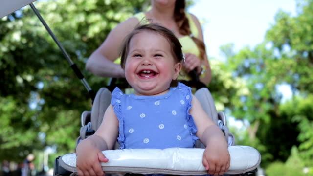 ベビーカーに座っていると、笑みを浮かべて彼女の母親と一緒に女の赤ちゃん - 女の赤ちゃん点の映像素材/bロール