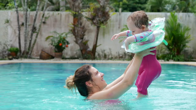 baby girl with inflatable float playing with mom in the swimming pool - inflatable stock videos and b-roll footage