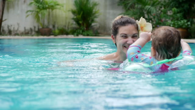 baby girl with inflatable float with mom in the swimming pool - inflatable stock videos and b-roll footage