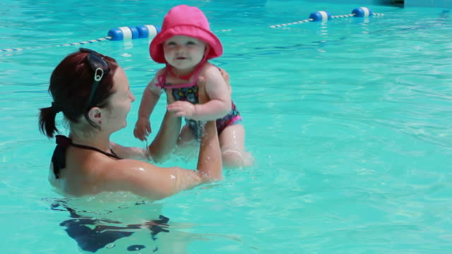 baby girl with mom at the pool - one piece swimsuit stock videos & royalty-free footage