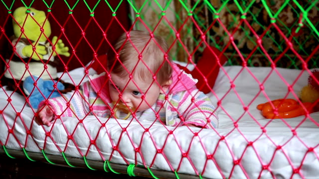 baby girl with pacifier lying in the crib - lying on front stock videos & royalty-free footage