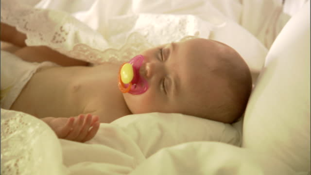 vídeos de stock, filmes e b-roll de cu, baby girl (6-9 months) with pacifier lying on bed - bico