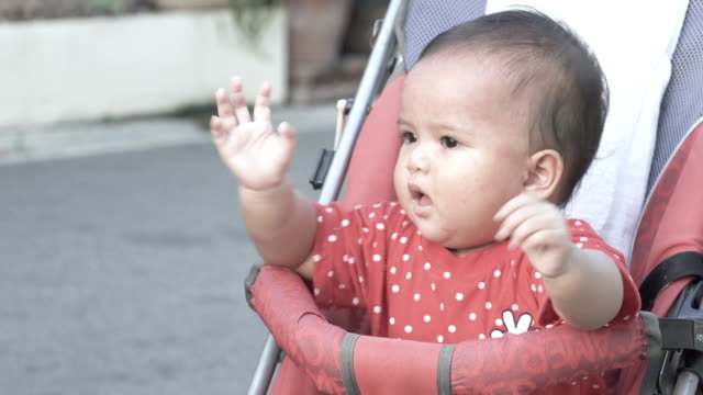 Baby girl with red spots on skin sitting in stroller. A kid is illness. Baby girl waving hands.