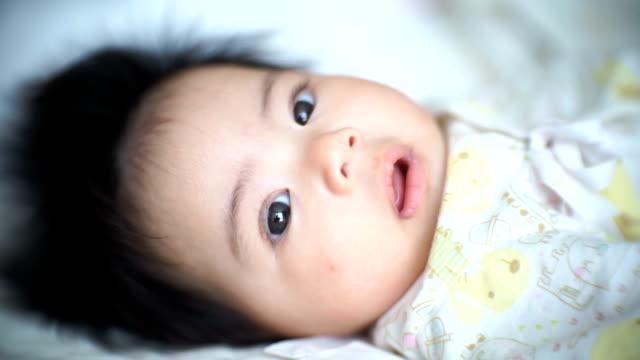 赤ちゃん女の子笑顔でベッドに横たわって - 生後1ヶ月点の映像素材/bロール
