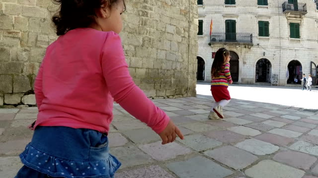 baby girls walking along the narrow street of the old town - montenegro stock videos & royalty-free footage