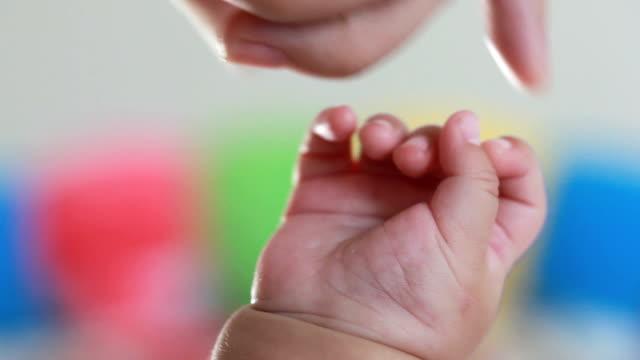vídeos de stock, filmes e b-roll de mão de bebê - carinhoso
