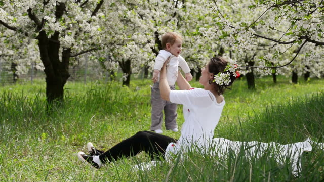 Baby held by his mother in the meadow