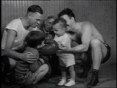 vídeos y material grabado en eventos de stock de 1946 baby in boxing gloves playfully hits young boy / usa - 1946