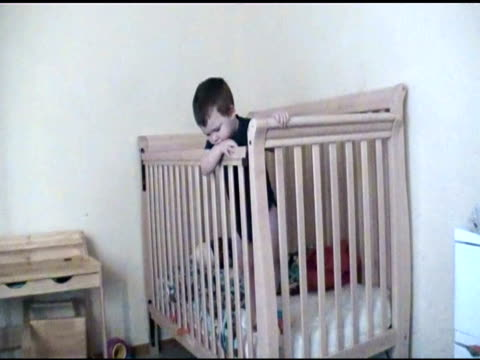 / baby in crib drinking from bottle and then tries to escape to retrieve dropped bottle / baby falls back into crib after first try and then... - オクラホマ州点の映像素材/bロール