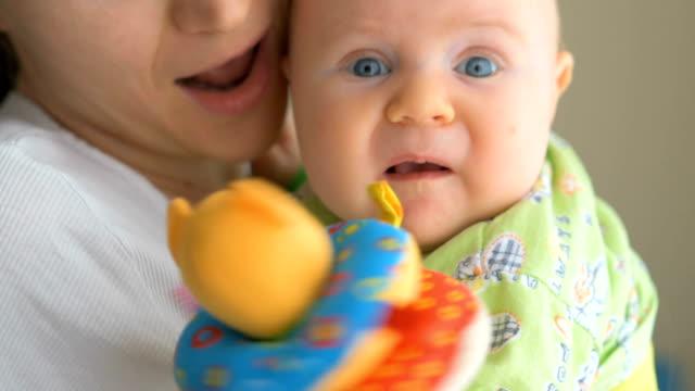 vídeos de stock e filmes b-roll de baby in tender arms of his mother - 2 5 meses