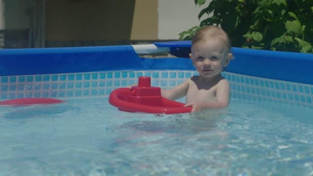 baby in the pool - neonati maschi video stock e b–roll