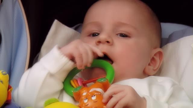 baby in the pram sucks a rattle - medium shot - sideways glance stock videos & royalty-free footage