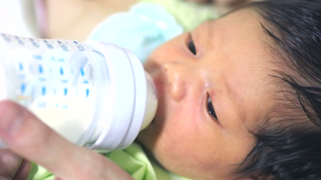 baby infant suckling milk from bottle - milk bottle stock videos & royalty-free footage