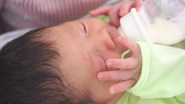 stockvideo's en b-roll-footage met baby infant suckling milk from bottle - alleen één jongensbaby