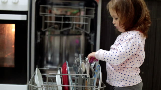 baby is playing with a kitchen brush around dishwasher - lavastoviglie video stock e b–roll