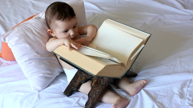 baby is playing with book - small stock videos & royalty-free footage