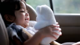 baby  is sitting on safety car seat and play with her teddy bear