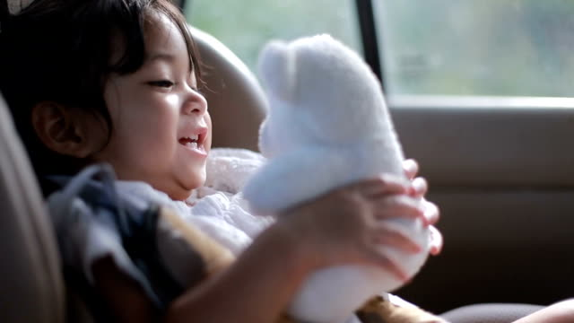 vídeos de stock e filmes b-roll de baby  is sitting on safety car seat and play with her teddy bear - fotografia da cabeça
