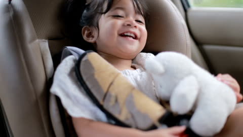 baby  is sitting on safety car seat and play with her teddy bear - car interior stock videos & royalty-free footage