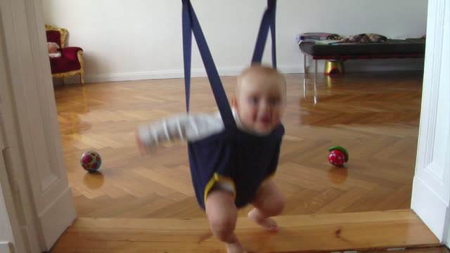 ms baby (8-9 months) jumping in baby bouncer / berlin, germany - jumping stock videos & royalty-free footage