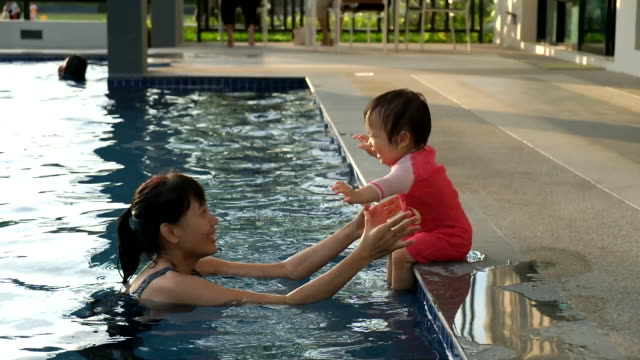 baby jumping into the pool to her mother - piscina pubblica all'aperto video stock e b–roll