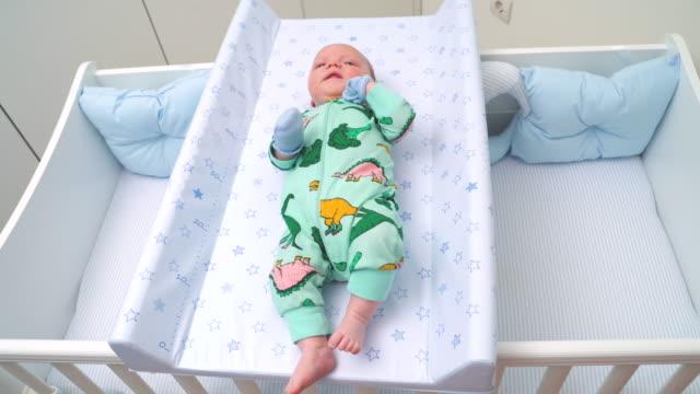 baby legt auf wechselnden mattentisch über seine krippe breite ansicht - ein männliches baby allein stock-videos und b-roll-filmmaterial